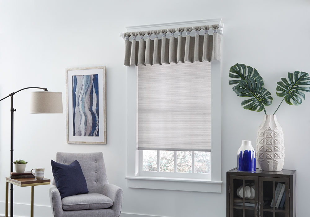 White Genesis® roman shade with Interior Masterpieces valance hanging on a white custom rod with finials in a room with white walls and a blue painting and white chair with a blue Interior Masterpieces® accenting pillow