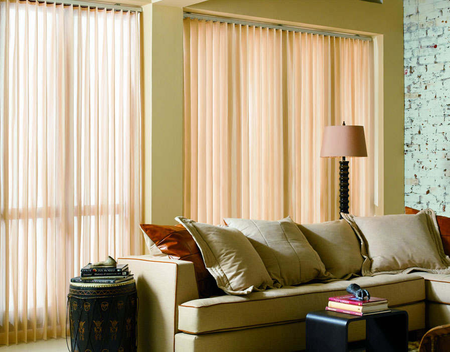 Two large Sheer Visions® Vertical Blinds hanging in a window with a couch and lamp in front