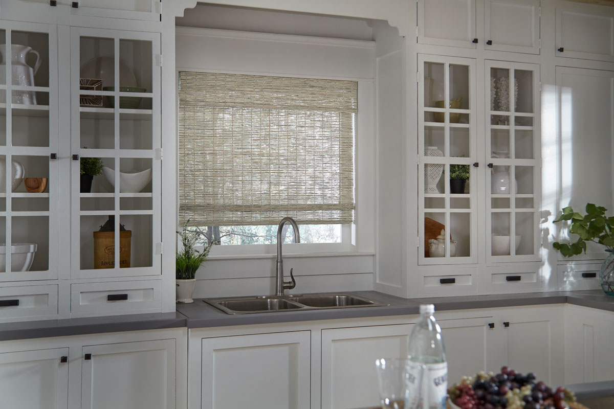 Light colored Manh Truc® Woven Wood Shade behind a kitchen sink and in between cabinets