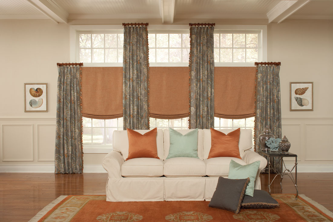 dark orange Interior Masterpieces® fabric shades with gran floral patterned draperies hanging on dark brown custom rods with rings and finials and accenting custom pillows on a couch