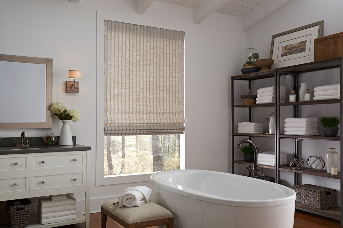 a tan Genesis® Hobbled Roman Shade in a bathroom behind a white stand alone tub next to shelves with towels