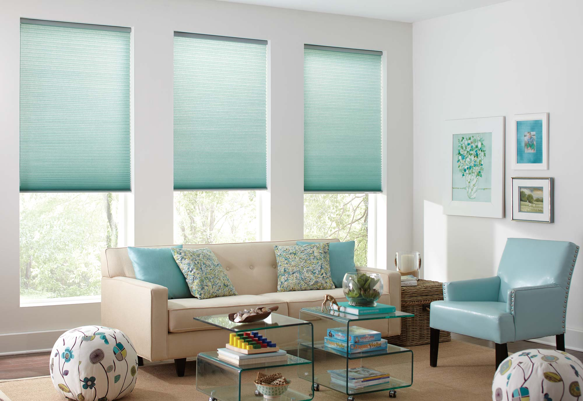 Three aqua colored Parasol® Cellular Shades hang in the windows of a bright family room with custom blue and patterned pillows on a modern cream couch.