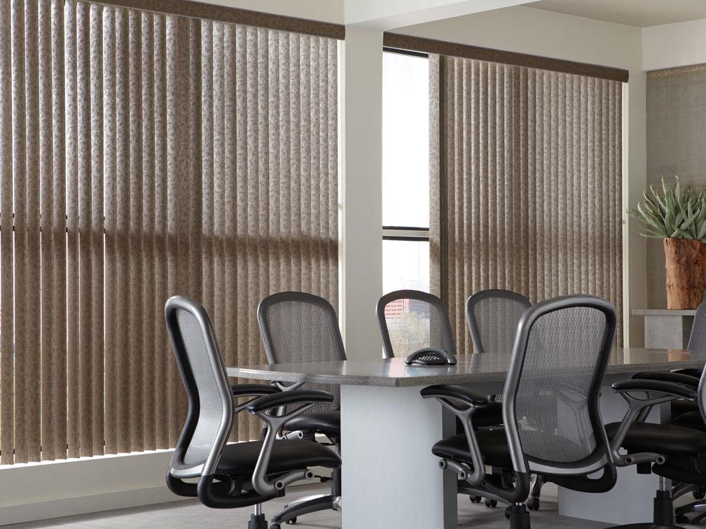 Brown Discoveries® Vertical Blinds in an office with gray chairs and desk in front