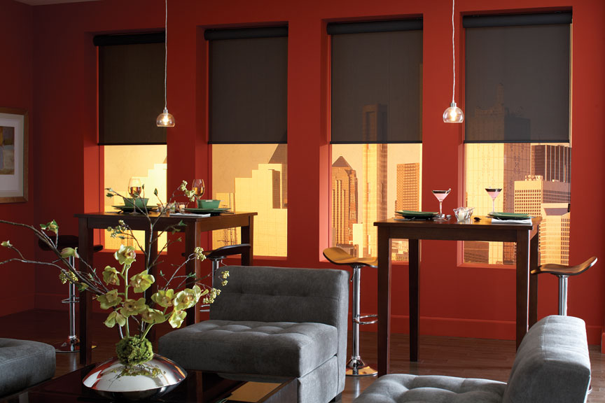 A dining room with dark, light filtering Genesis® Roller Shades