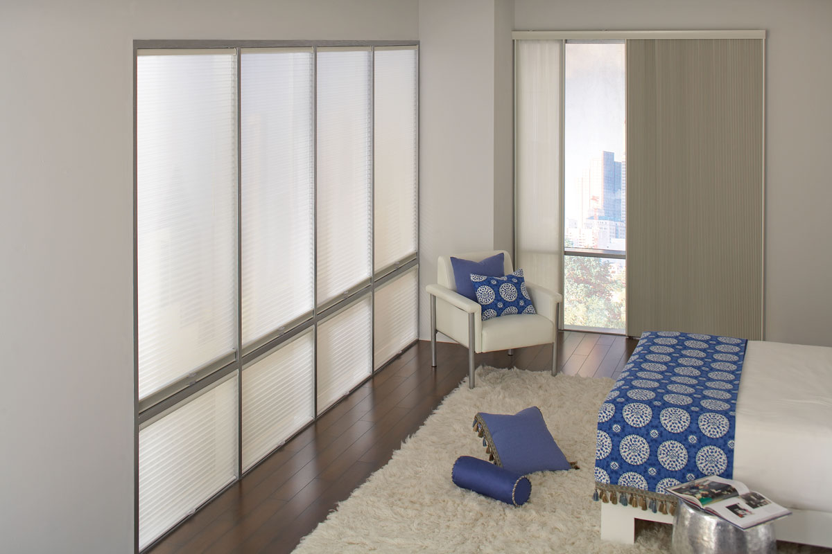 Large picture windows on one side of the room with Parasol® Duo-Lucent Cellular shades in them and a Parasol® Glissade panel system on the other in a light tan material with a bed and chair that have custom bedding in a blue material