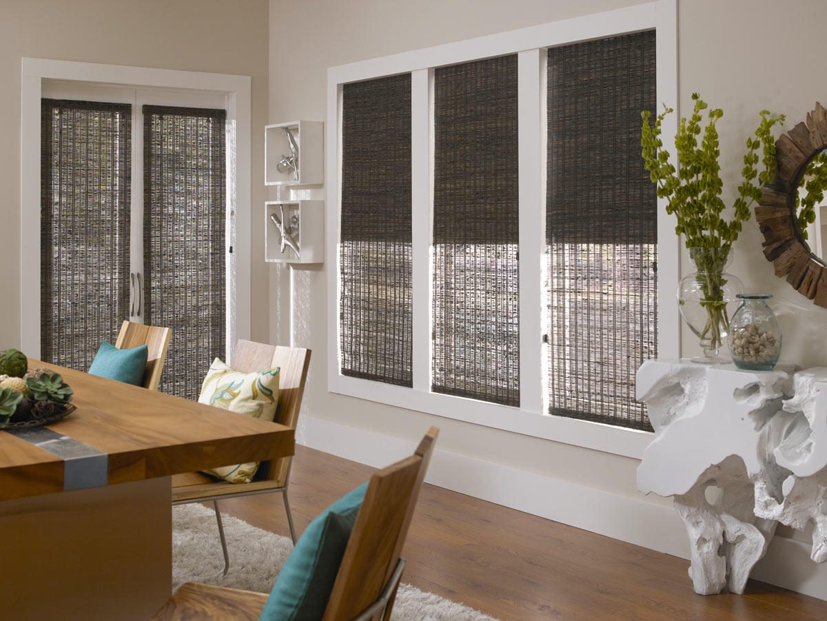 Several dark Manh Truc® Woven Wood Shades in a dining area with a brown table and chairs that have blue and green floral patterned custom pillows on them