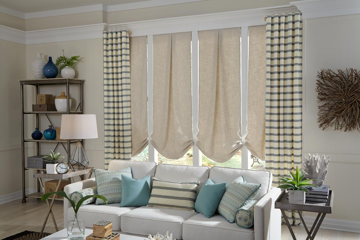 4 tan Interior Masterpieces® Roman Shades with pleats and back tab draperies hanging on either side behind a couch that has several different light green and blue custom pillows