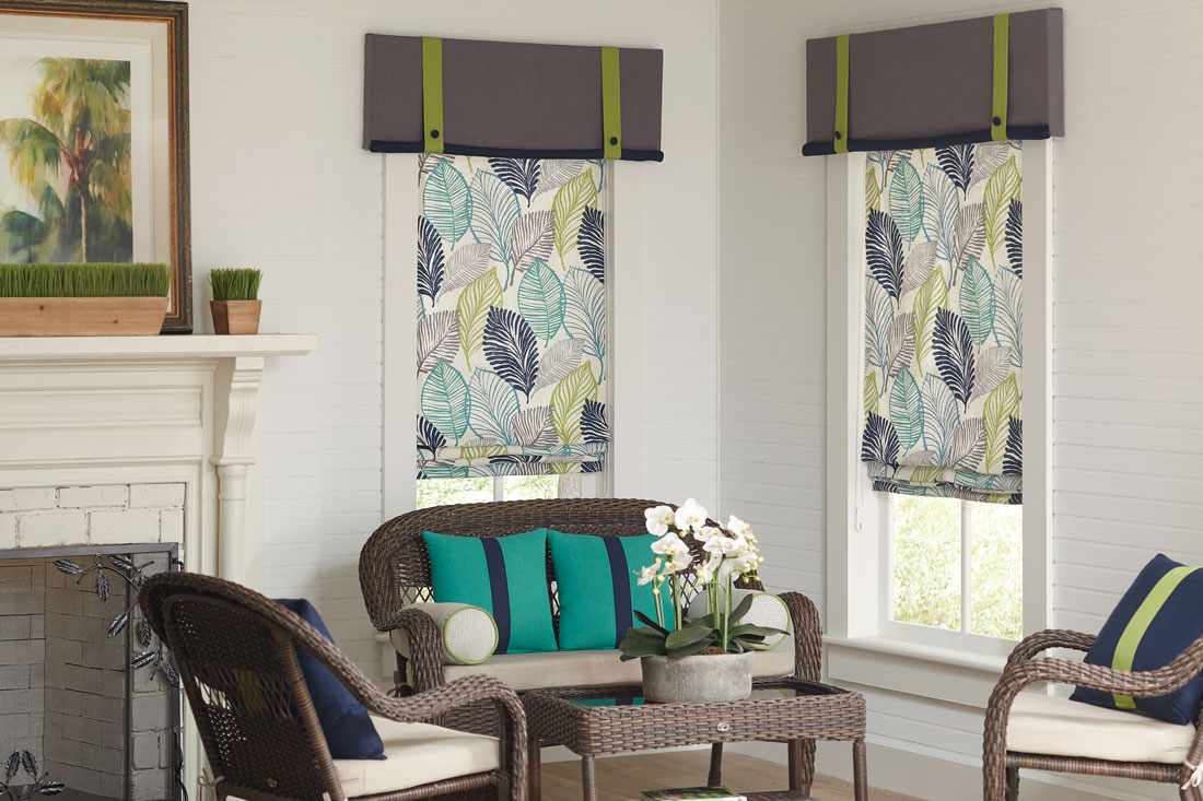 Two blue, teal, yellow, and gray floral patterened Interior Masterpieces® fabric shades with accenting fabric gray and lime green cornices in a room with benches that have teal and blue custom pillows