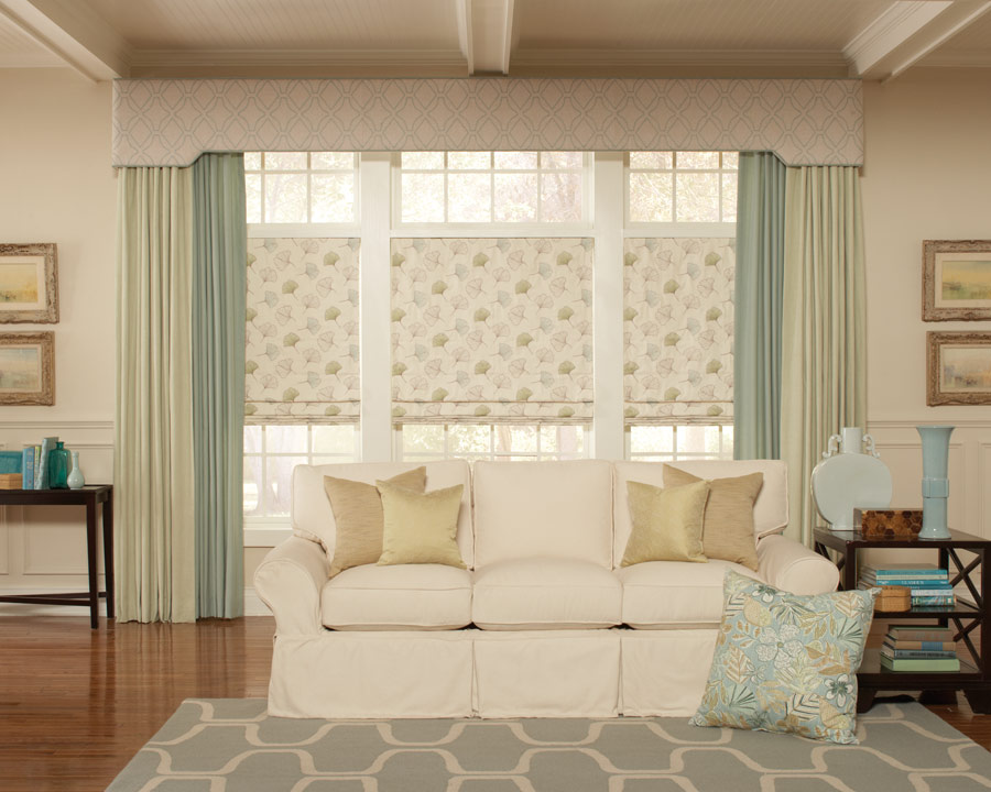 Interior Masterpieces® cornice spanning a large picture window with matching draperies and fabric shades underneath with a couch that has custom pillows in front