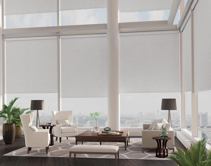 Several tan colored Genesis® Motorized Roller Shades in a high rise corner dining area with white chairs and a brown table in the foreground