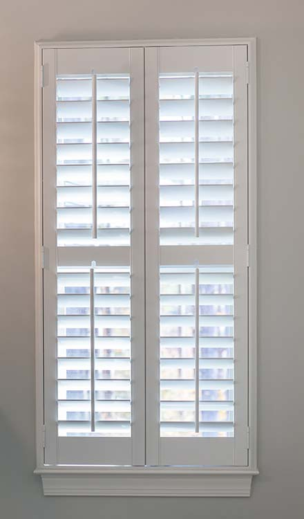 closeup view of Parke® Shutters in a window with a divider rail