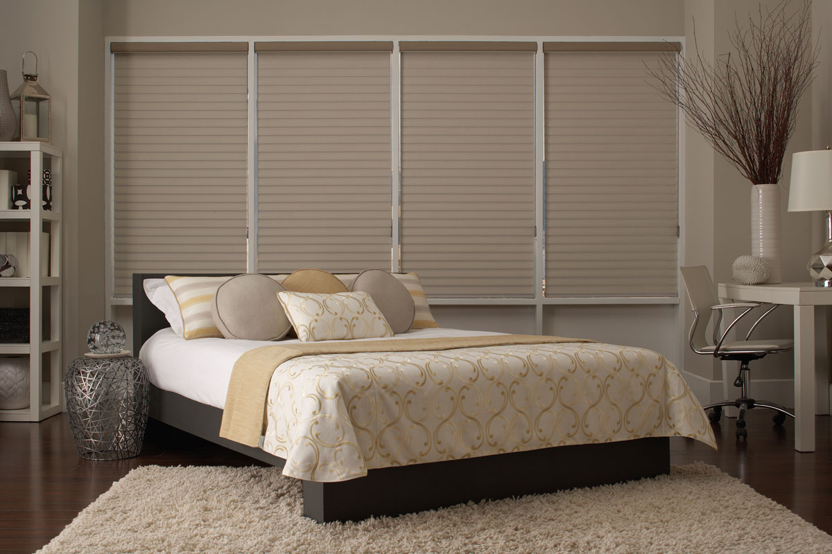 Several tan Tenera® sheer shades in the closed position in a tan bedroom with a bed that has custom Interior Masterpieces® pillows and blankets on it