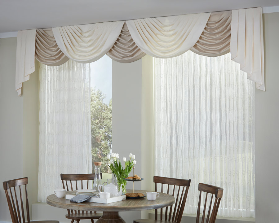Interior Masterpieces® draperies with festooned draperies valance spanning a dining room wall with a table and chairs in front