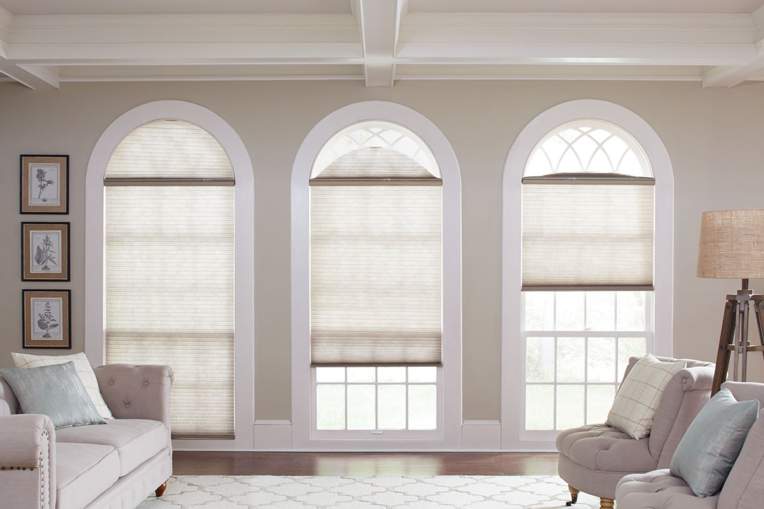 Three Parasol® Cellular shades in 3 tall windows with a rounded top that have Slide Arch Specialty Shaped Parasol® shades in them
