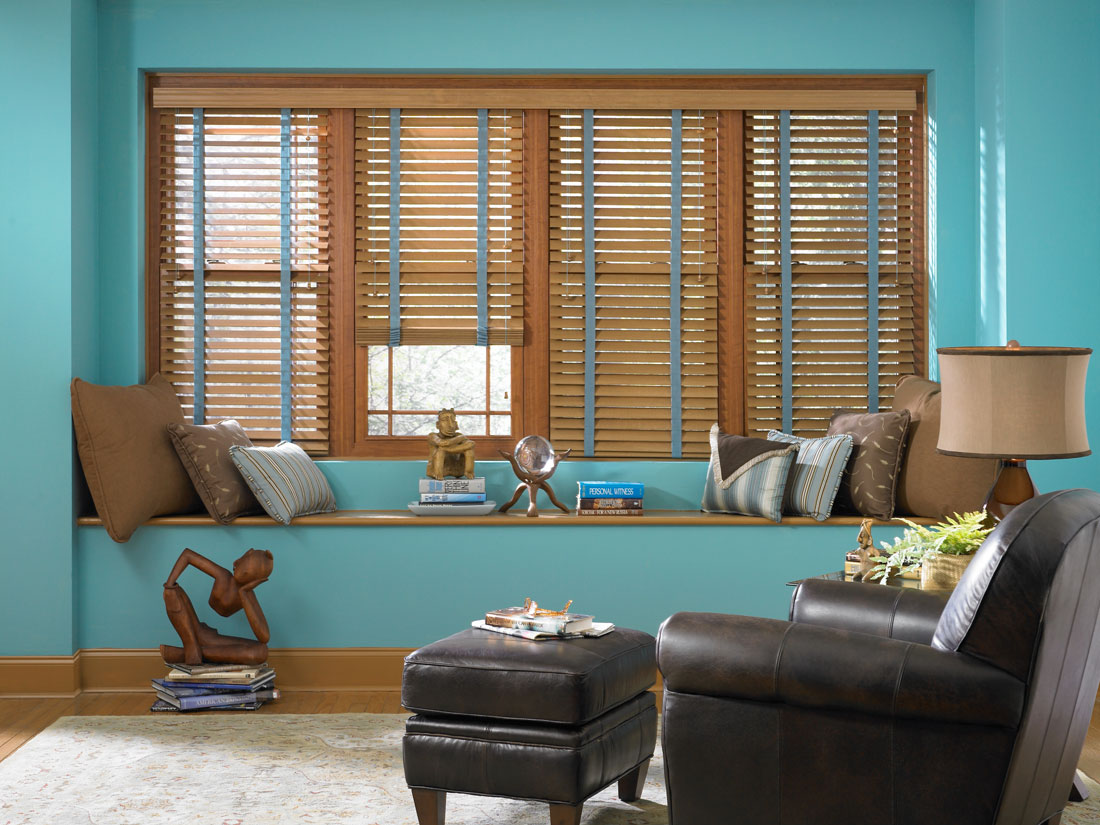 four brown Heartland Woods® Wood Blinds with blue Banding in a room with blue walls and a black chair