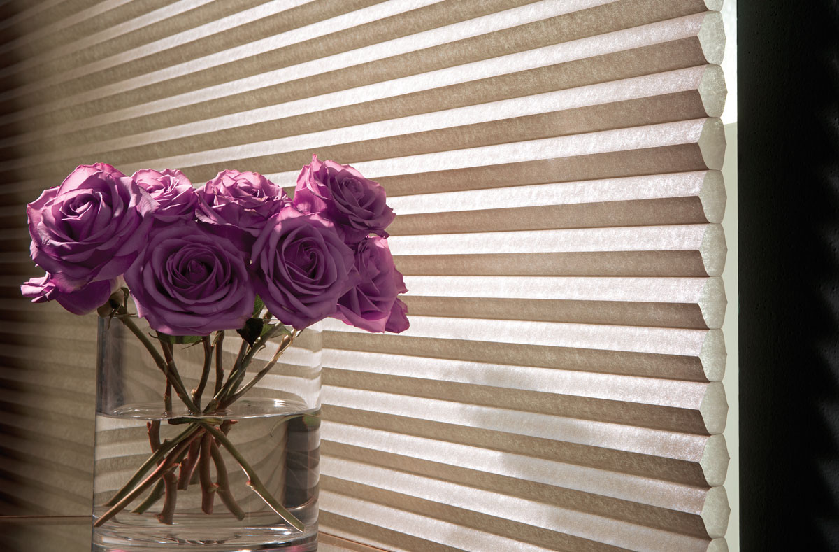 Close up of a tan Parasol® Cellular shade material with purple roses in front
