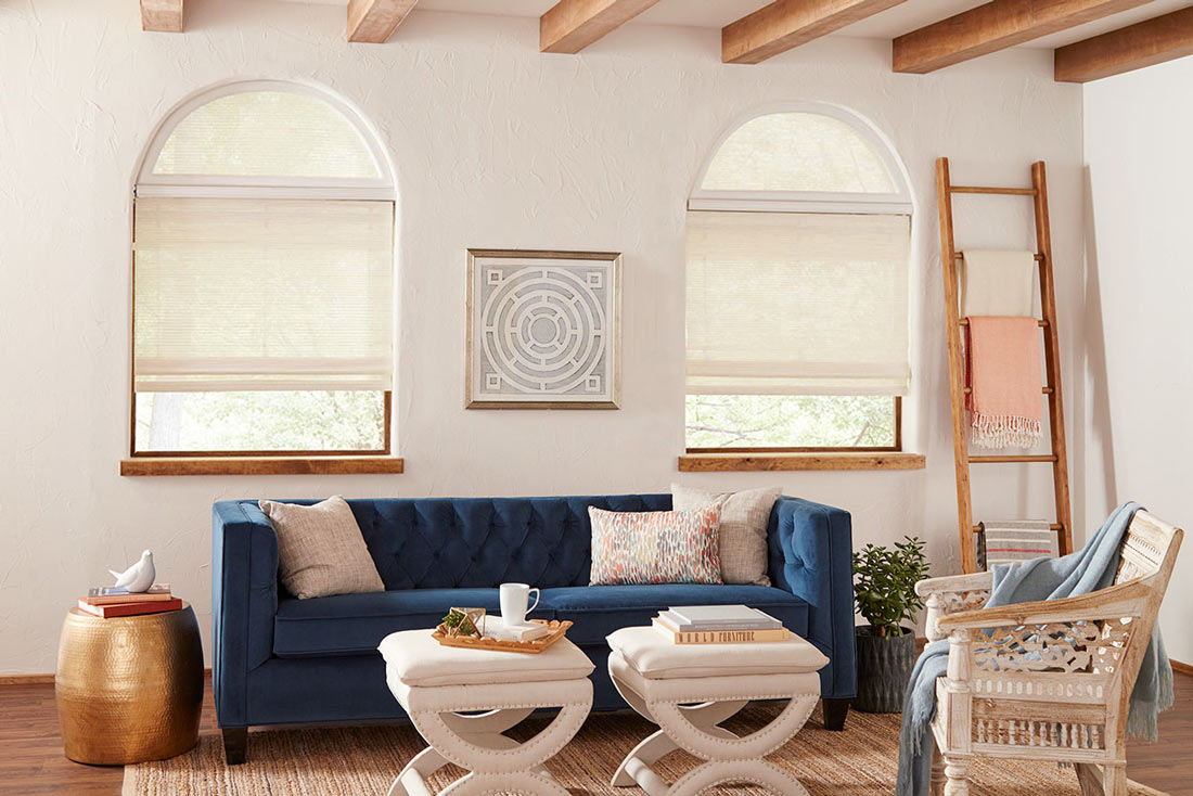 two white Manh Truc® Woven Wood Shades with  half circle Custom Shapes on top & Palladian Shelf in between behing a blue couch with custom pillows