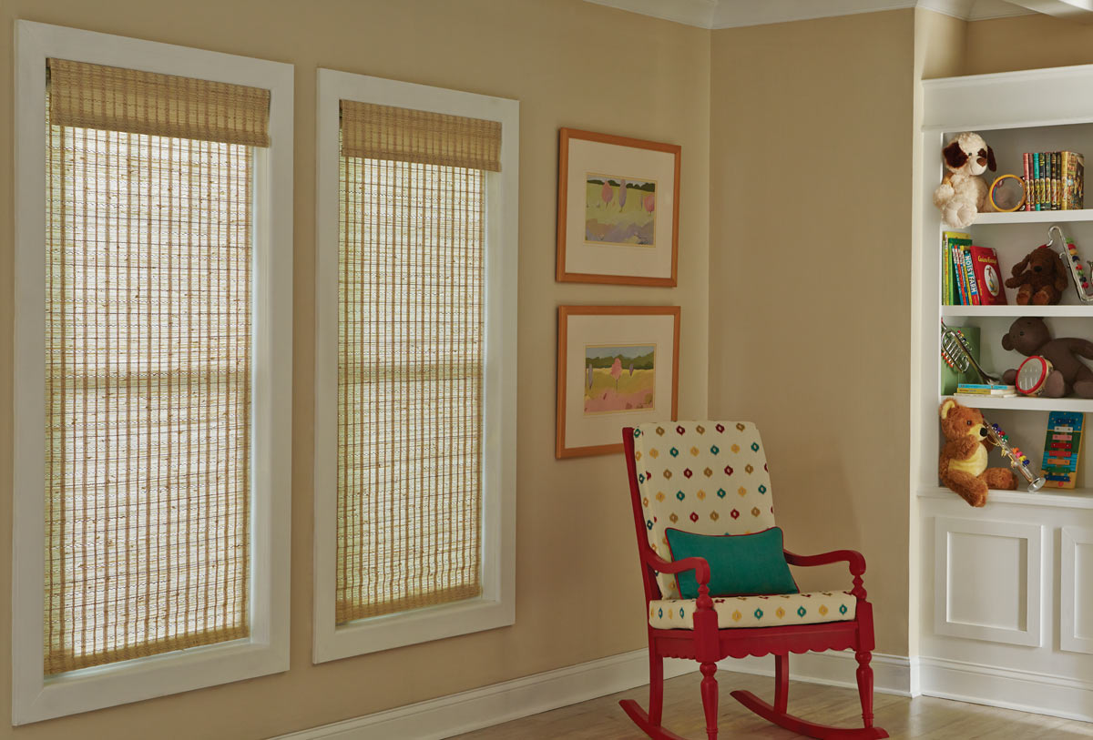 Two light brown grassy Manh Truc® Woven Wood Shades in the close position next to a brightly colored pink and polka dot chair