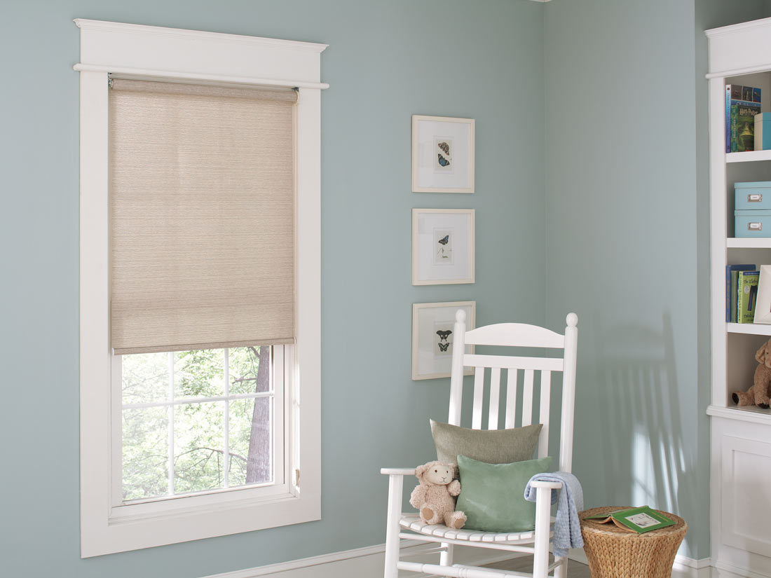tan Genesis® Roller Shades against blue walls with a white chair nearby and a stuffed animal on it