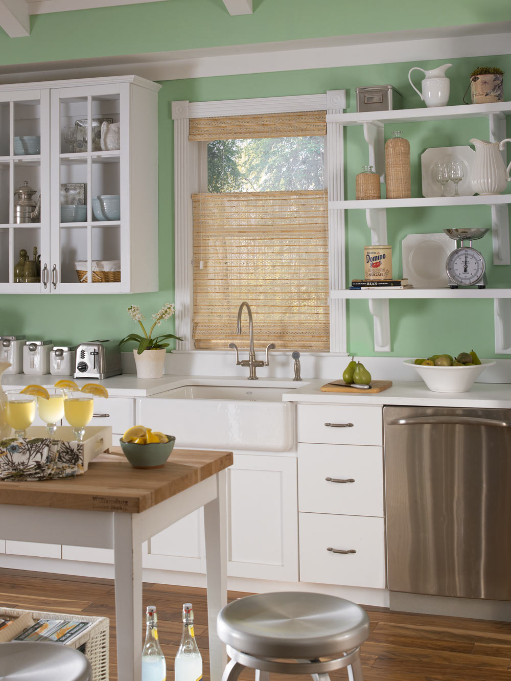 Light brown Manh Truc® Woven Wood Shade against light green walls in a kitchen