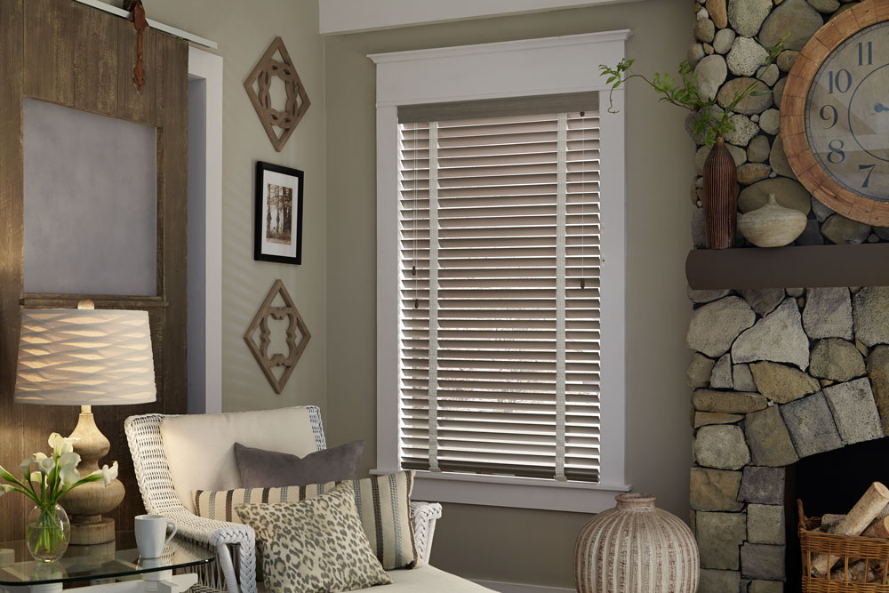 Gray Heartland Woods® Wood Blinds with white Decorative Tape next to a chair with custom pillows from the Interior Masterpieces® line