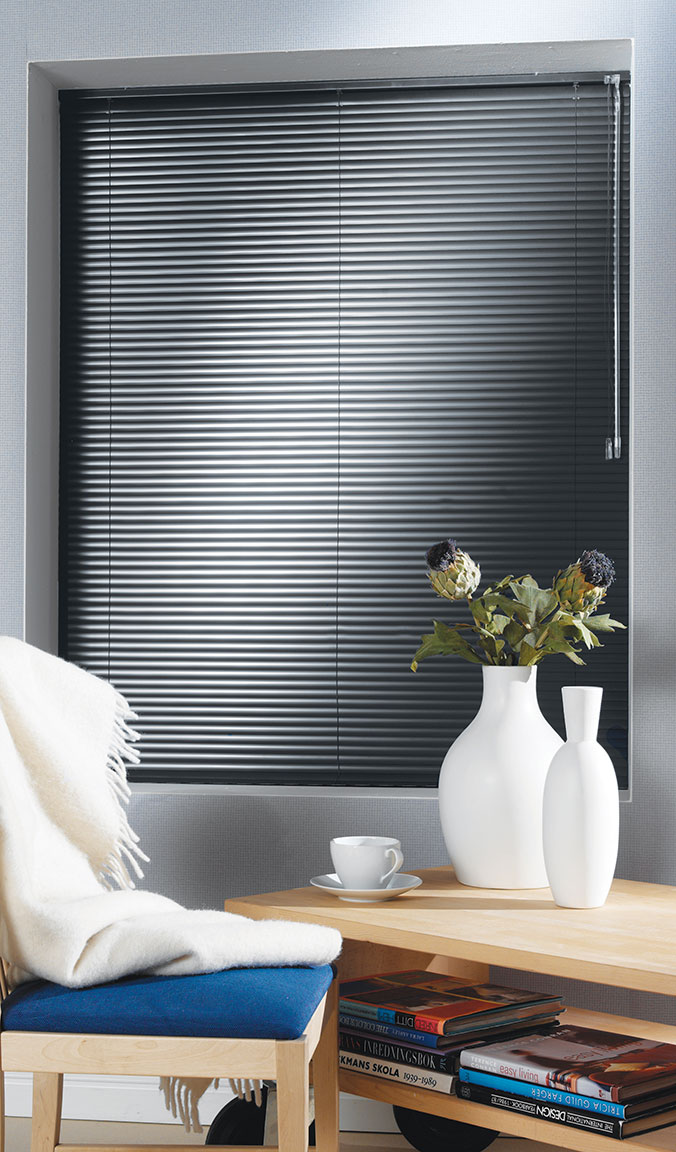 Dark Classic Collections® Aluminum Blinds in a room with light gray walls with a chair and table in the foreground