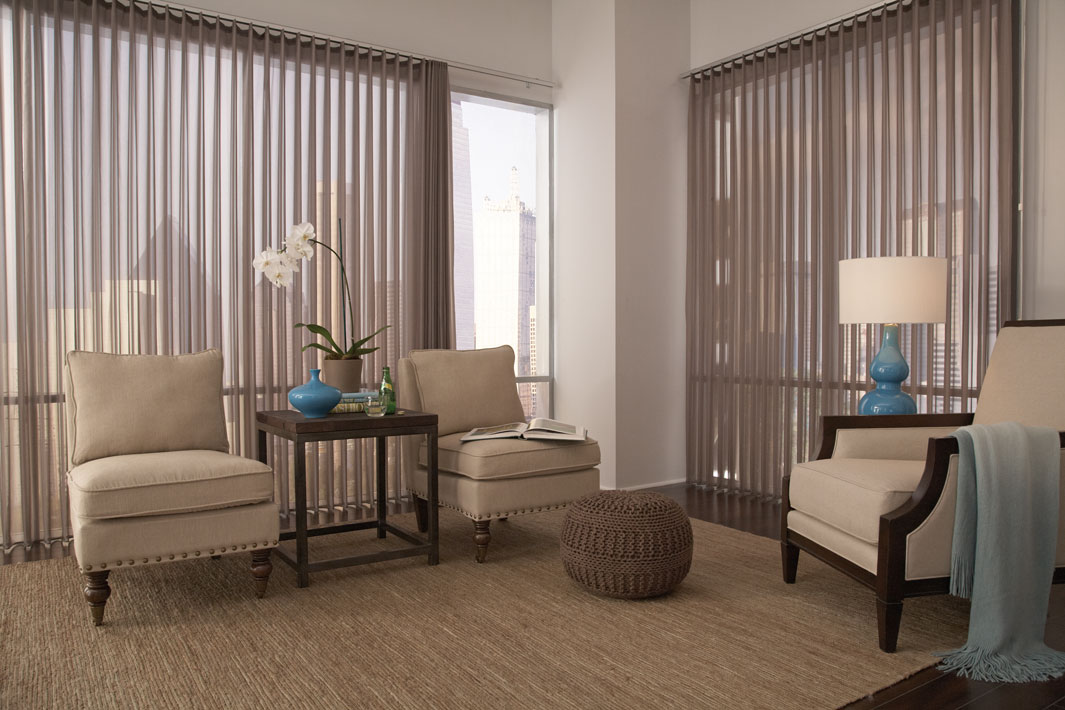 Brown colored Sheer Visions® vertical blinds in two large picture windows with tan furniture in the room
