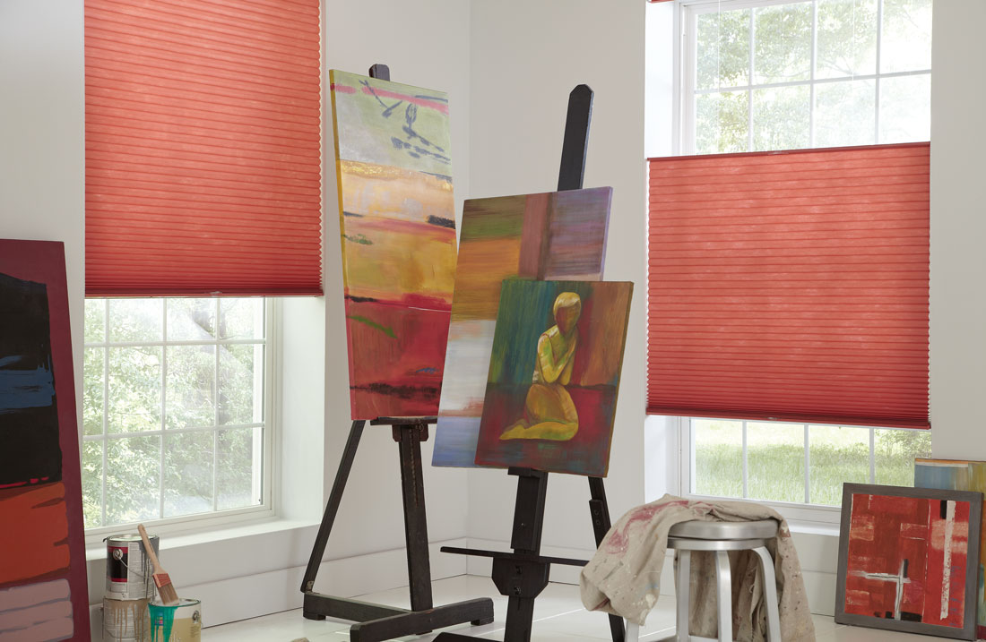 Close up shot of 2 Parasol® Top Down Bottom Up shades positioned at different heights with art on easels sitting in front