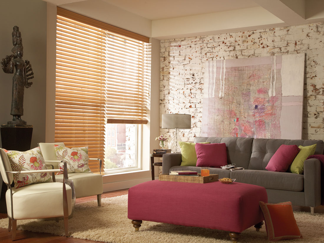 light Brown Fidelis® faux wood blinds in a room with a gray couch and maroon ottoman with green and maroon custom pillows on it next to white chairs with floral printed custom pillows