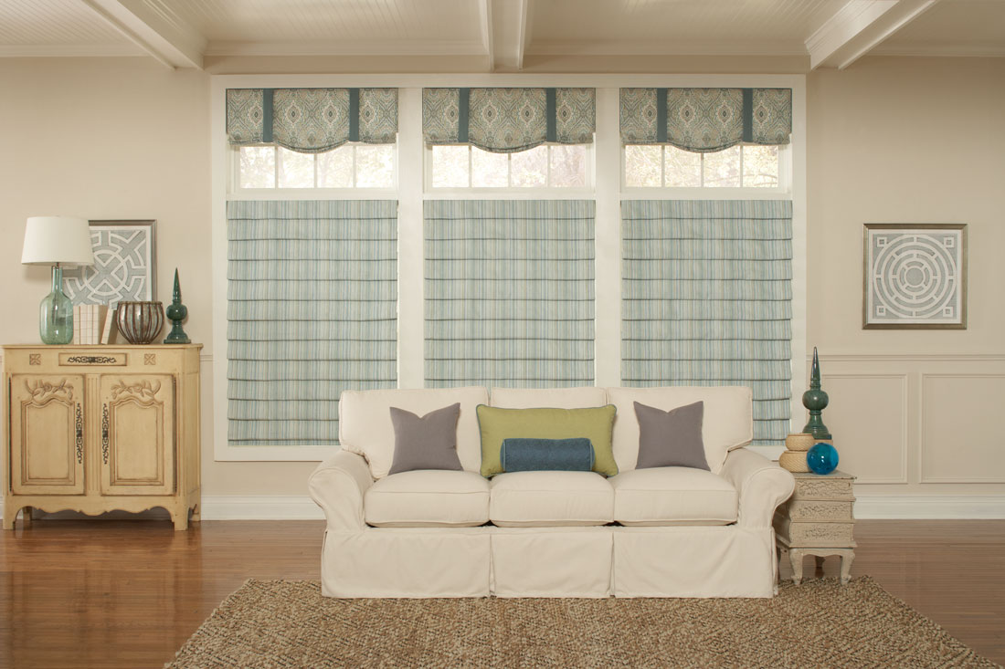 three light greenish blue striped Interior Masterpieces® fabric shades with fabric wrapped cornices above each behind a couch with custom gray, yellow, and blue pillows