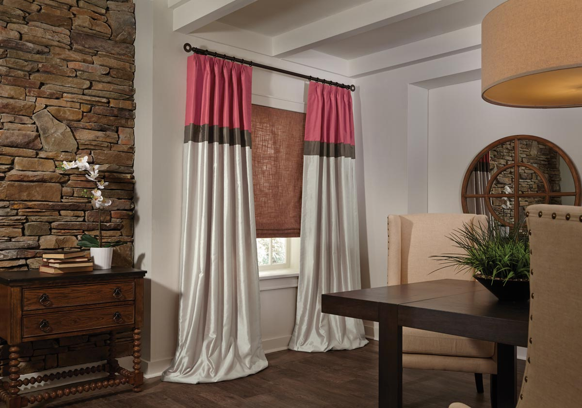 Long flowing light red and tan Interior Masterpieces® draperies pooling on the floor in front of a red flat roman shade