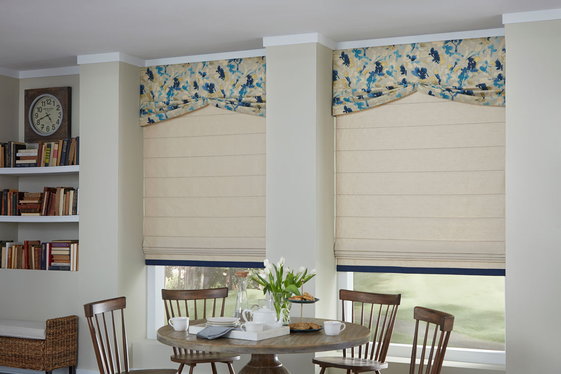 Two tan Interior Masterpieces® fabric shades with custom fabric valances that have a blue and yellow floral pattern behind brown table and chairs