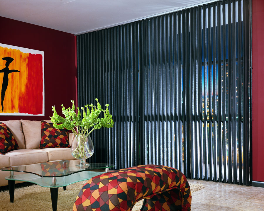 Black Discoveries® Vertical Blinds in a large picture window against a red wall with tan furniture and a red and orange painting