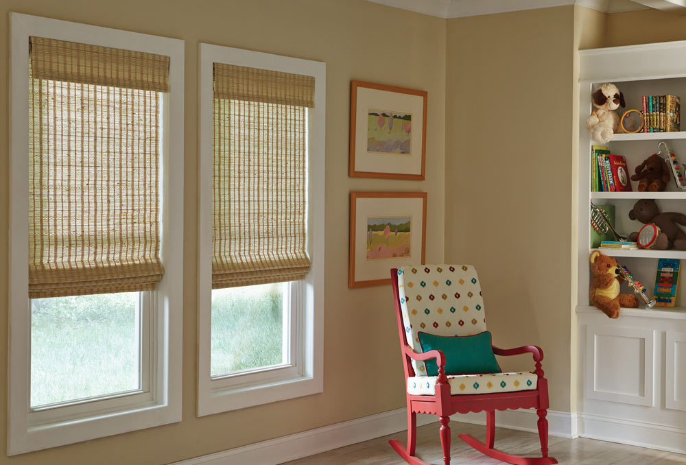 two light brown Manh Truc® Woven Wood Shades behind a polka dot and pink chair