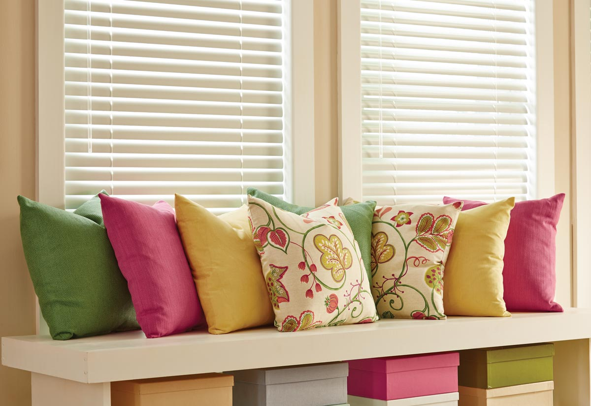 Several brightly colored Interior Masterpieces® Custom Pillows in front of white Classic Collection® Aluminum Blinds