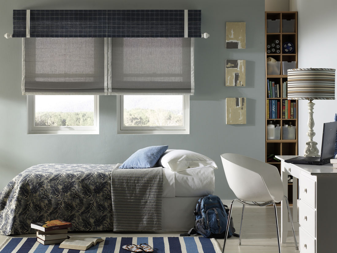 Gray Manh Truc® woven wood shades with white banding and a blue plaid Interior Masterpieces® Valance that has a white custom rod with finals