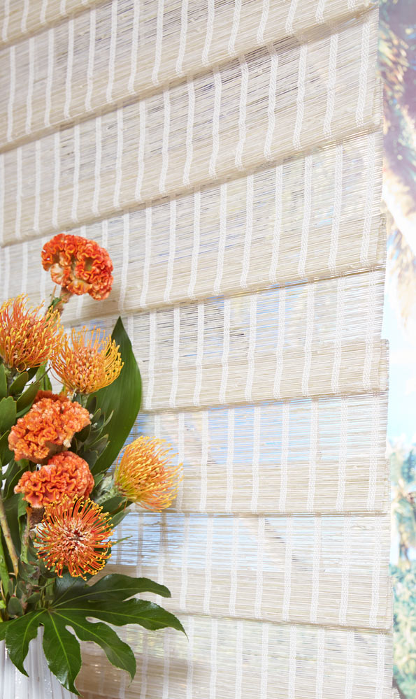 close up of white colored of Manh Truc® Woven Wood Shades with orange flowers in the foreground