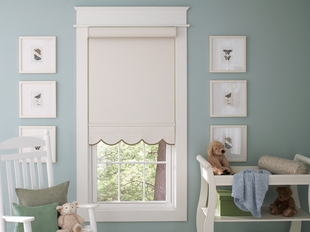 light tan Genesis® Roller Shades with Scalloped Hem and brown Decorative Trim against a white frame with blue walls in a child's room with a changing table and stuffed animals nearby
