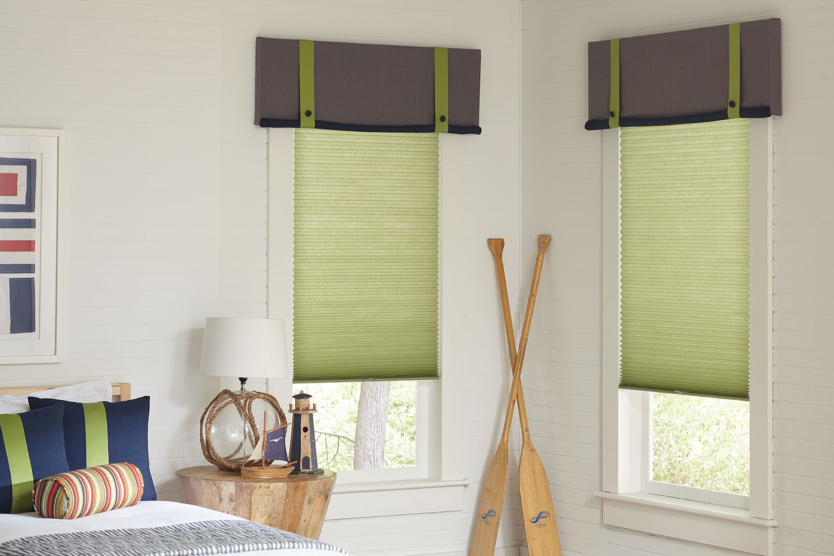 Light, grassy green cellular shades hang in the two corner windows of a child's bedroom featuring nautical accessories, custom matching valances in gray and pillows in navy with green accents.