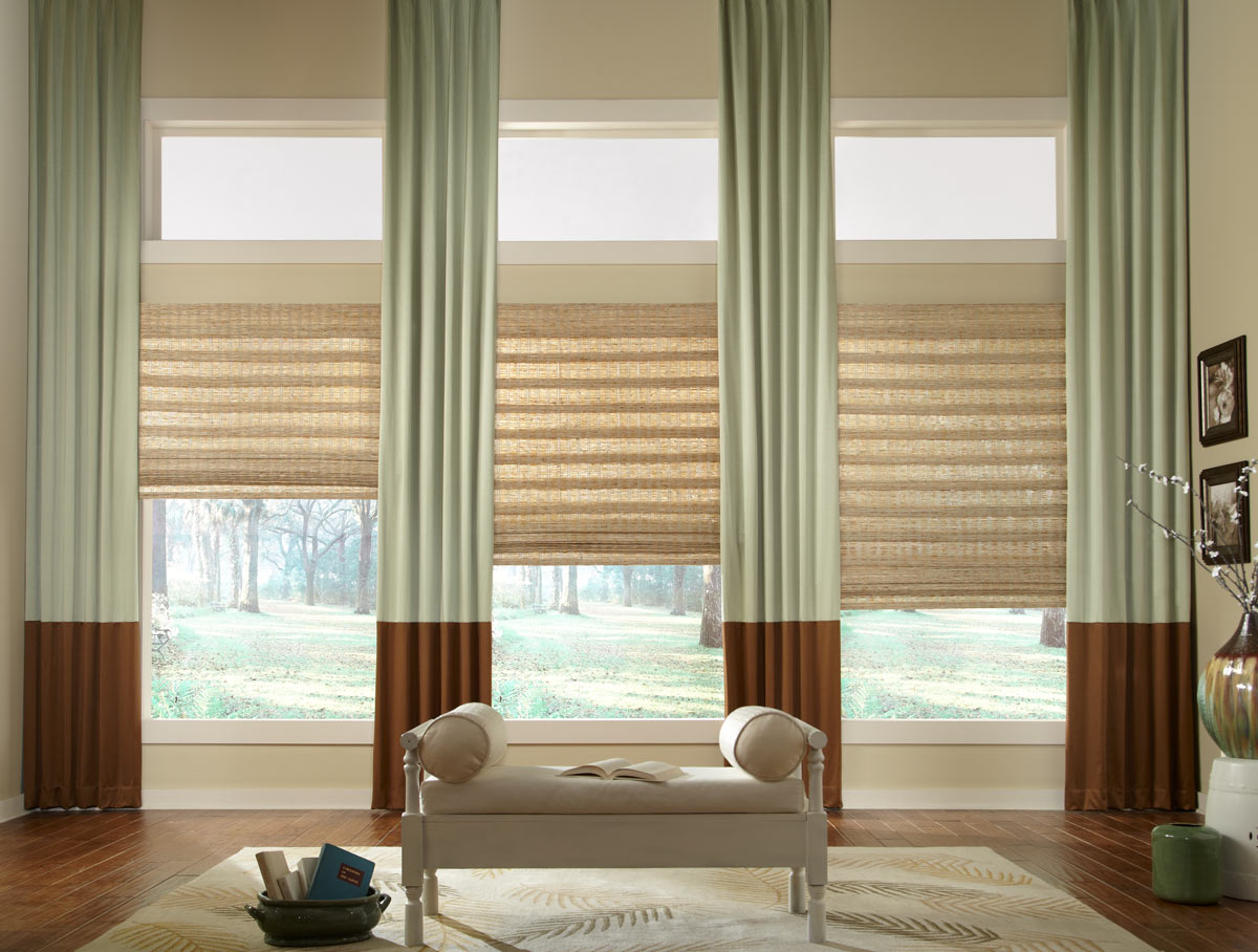 several light brown Manh Truc® Woven Wood Shades with light green and dark brown Interior Masterpieces® Draperies hanging between with a light brown chair in the foreground