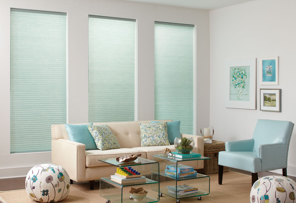 Three Parasol® Cellular shades in a light blue color in front of a tan couch with matching pillows and a blue matching chair