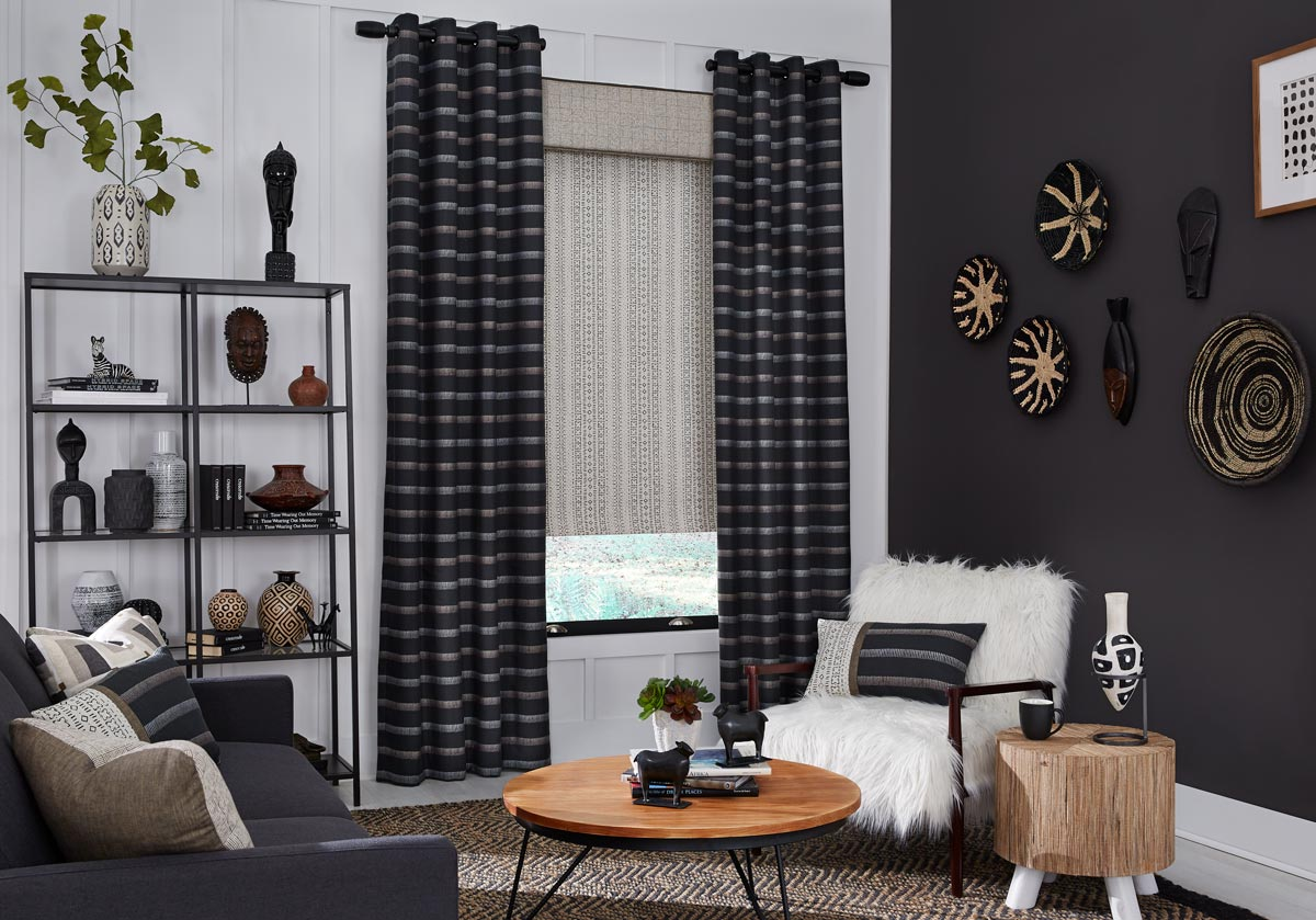 Dark Interior Masterpieces® grommet panels in front of a tan fabric wrapped cornice and fabric shade in a room with chairs and custom Interior Masterpieces® pillows
