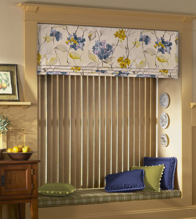 Blue and green floral valance accent vertical blinds hanging in a window with a bench box cushion accented with blue and green pillows.
