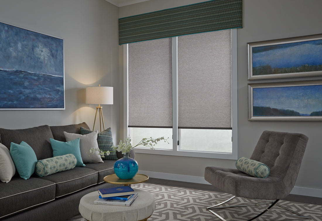 Two large gray Genesis® Roller Shades with a green and yellow striped Interior Masterpieces® Fabric Cornice spanning both shades and a dark gray couch with accenting blue, gray and green Custom Pillows