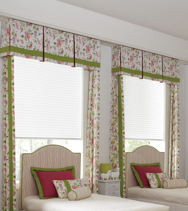 bedroom with two beds that have windows behind them with Parasol® cellular shades and custom Interior Masterpieces® cornices, draperies, and pillows that match in a light floral pattern