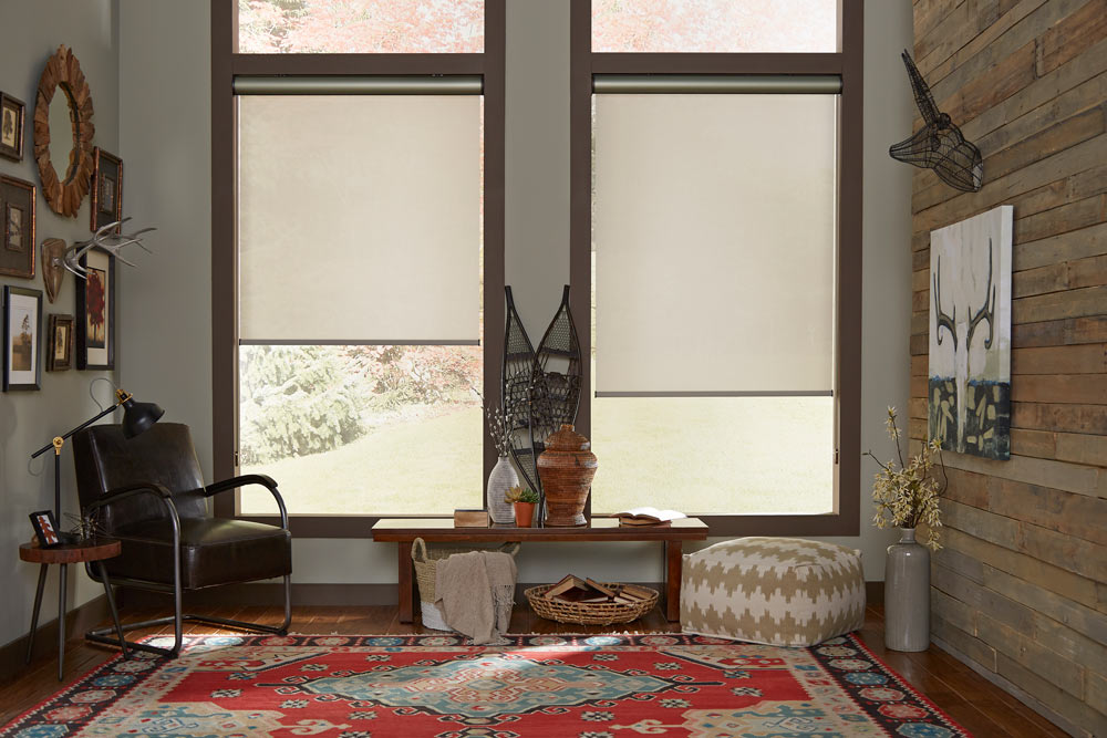 two large tan Genesis®  Roller Shades with bronze Cassettes in a room with gray walls and dark brown trim