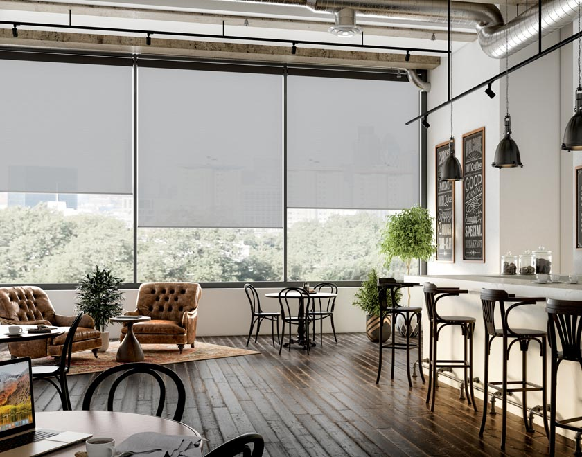 Several dark Genesis® Motorized Roller Shades in a restaurant with stools and a seating area with brown chairs and tables