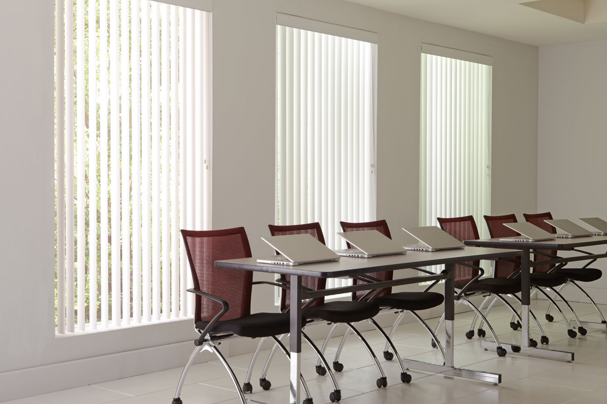 3 large windows with white colored Discoveries® Vertical Blinds in them in an office with several red chairs and laptops