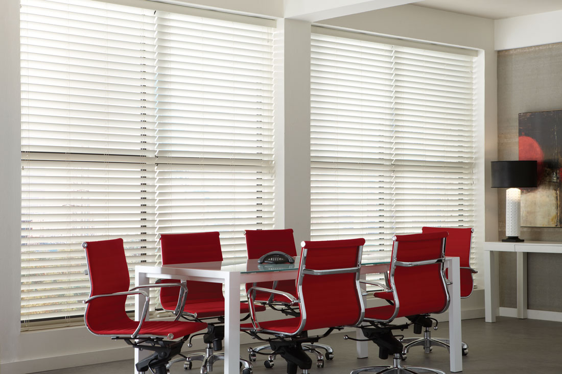 Large white Wonderwood® Wood Blinds in an office with red chairs and a metal table