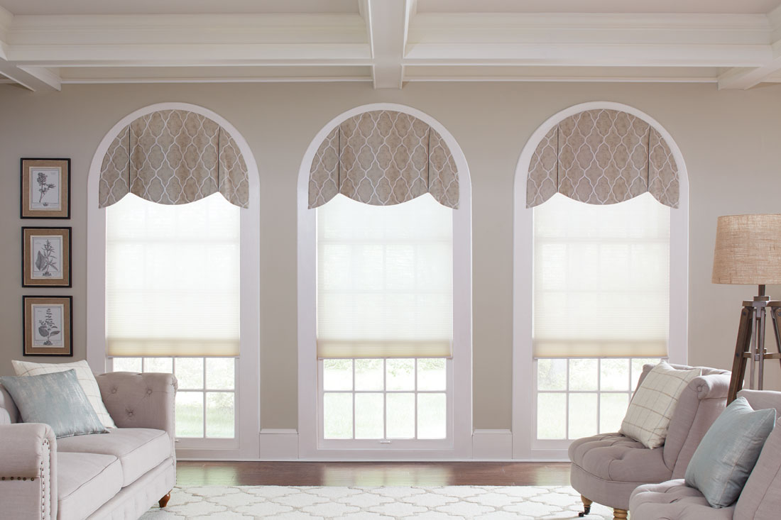 Three light colored Parasol® Cellular shades in windows with rounded tops that have custom Interior Masterpieces® Cornices on top
